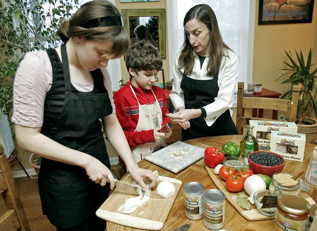 Julia Crews, 12, Tony Crews, 10, and their mom, Terry Crews, help prepare a Cuban meal at their Grayslake home. Father Julian Crews hopes to introduce more suburbanites to the bright and savory flavors from his ancestral home through his Old Havana Foods products.