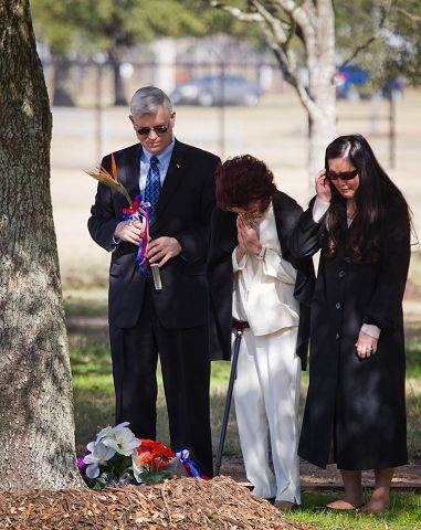 Johnson Space Center Director Michael L. Coats, left, stands with Lorena Onizaka and Darien Onizuka-Morgan, the wife and daughter of space shuttle Challenger astronaut Ellison Onizuka, after placing flowers on a memorial marker for Onizuka in the Astronaut Memorial Tree Grove during the annual National Day of Remembrance ceremony at the Johnson Space Center.