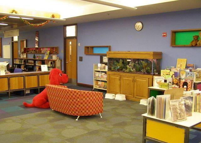 @SP Caption:Clifford, the big red dog, checks out the fish tank at the Mount Prospect Public Library.