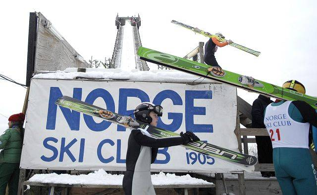 Hunter Smith, 9, of Fox River Grove, center, makes is way to the staircase of the K70 hill at the Norge Ski Club international tournament in Fox River Grove Sunday. Smith has been ski jumping for three years.