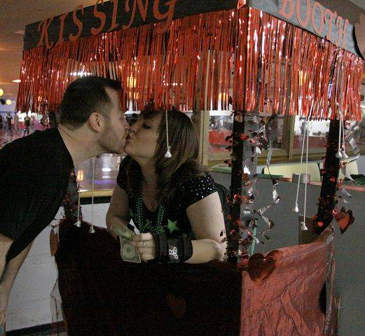 Jason Thalman, of Oswego, kisses Skip Bacon at the kissing booth at the DuPage Derby Dames fundraiser Sunday at the Aurora Skate Center in Aurora.