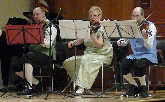 From left to right, John Brubaker, Lori Davis and Eric Stern play violin in Old Fezziwig's Band at the Gail Borden Public Library in Elgin Sunday, during an English country dance performance and lesson by Fermilab's newest dance group.