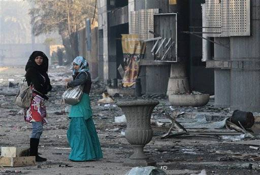 Women walk past a damaged shopping center in Cairo, Egypt, Monday. Police and garbage collectors appeared on the streets of Cairo Monday morning and subway stations reopened after soldiers and neighborhood watch groups kept the peace in many districts overnight.