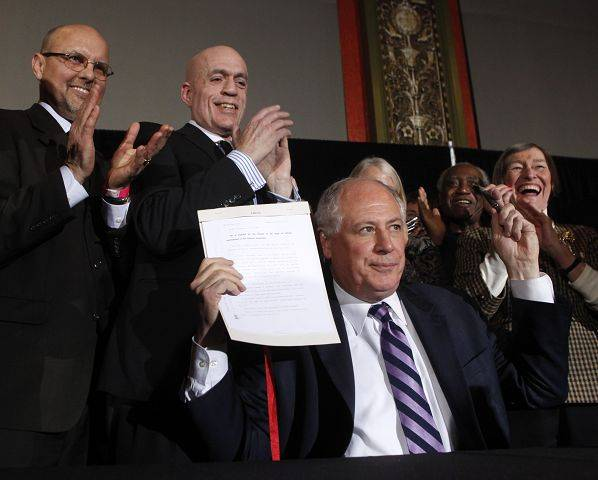 Illinois Gov Pat Quinn holds up the signed civil unions bill during ceremonies Monday in Chicago. Applauding behind Quinn are the legislative sponsors, state Sen. David Koehler, left, and state Rep. Greg Harris.