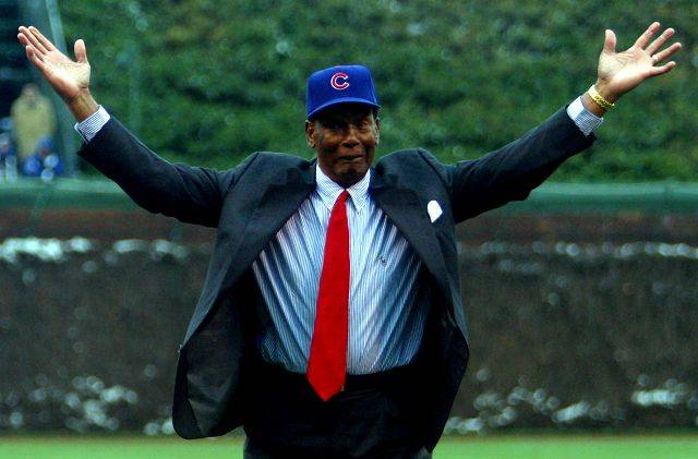 Cubs legend Ernie Banks gestures after tossing the ceremonial first pitch to fellow ex-cub Ryne Sandberg before Cubs home opening day Wrigley Field in 2003.