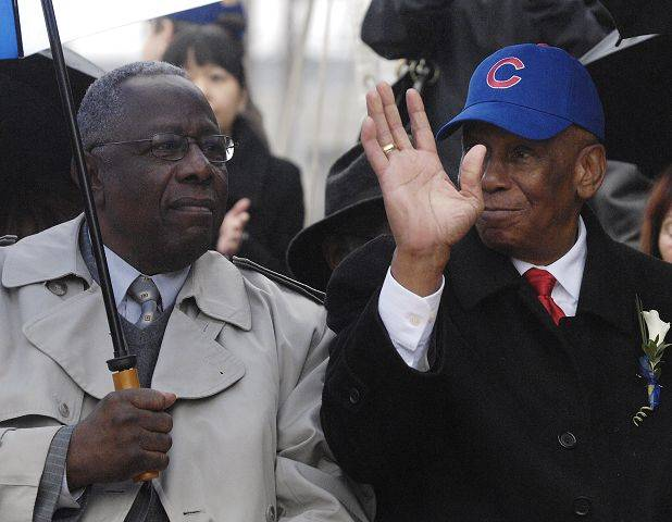 Ernie Banks gives a little wave to the fans as baseball great Hank Aaron sits nearby in April, 2008.