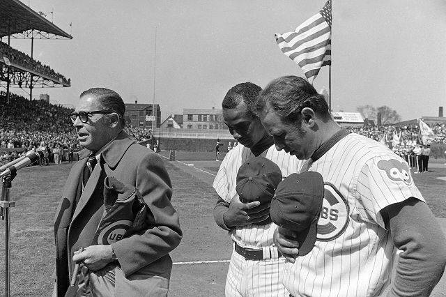 Chicago Cubs co-captains Ernie Banks and Ron Santo, right, bow heads as master of ceremonies Milton Berle leads opening-day crowd in prayer for safe return of Apollo 13 astronauts Tuesday, April 14, 1970 in Chicago. The Cubs played Philadelphia before a capacity crowd in Chicago.