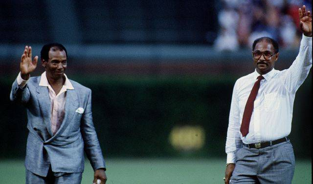 Cubs legends Ernie Banks and Billy Williams acknowledge the crowd before tossing out ceremonial first pitches for the first night game at Wrigley Field on August 8, 1988.