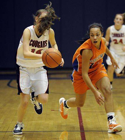 Conant's Alyssa Rawleigh gets blinded by her own hair as she chases down a loose ball with Hoffman Estates Jada Stotts Thursday.