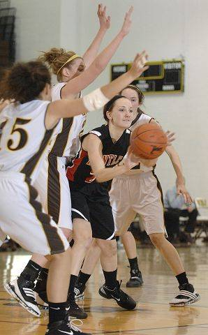 Huntley's Abbey Shaw passes around a block by Jacobs' Payton Berg and Melanie Schwerdtmann Wednesday.