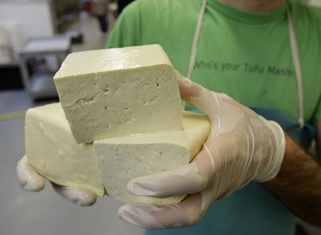 Andrew Marcus as he holds up blocks of firm tofu at the Hodo Soy Beanery in Oakland, Calif. In Hodo Soyís 12,000-square-foot factory, organically grown soy beans are soaked, ground and boiled creating a rich soy milk to which the natural coagulant calcium sulfate is added.