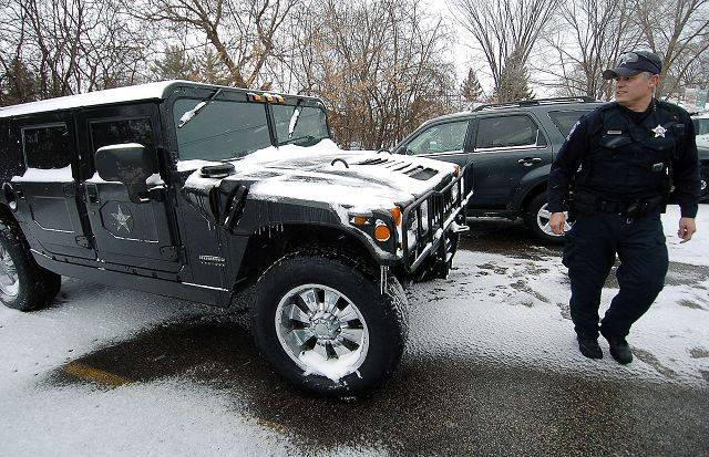 Round Lake Park police officer Waymon Vela walks by the department's Army surplus Hummer, which was ready to go Tuesday in case of emergency during the blizzard.