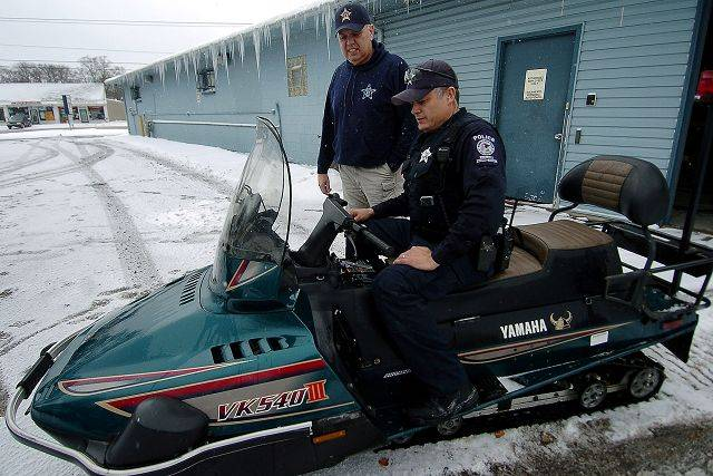 Round Lake Park Police Chief George Filenko, left, and officer Waymon Vela examine one of the department's two Arctic Circle-grade snowmobiles previously owned by the Navy.
