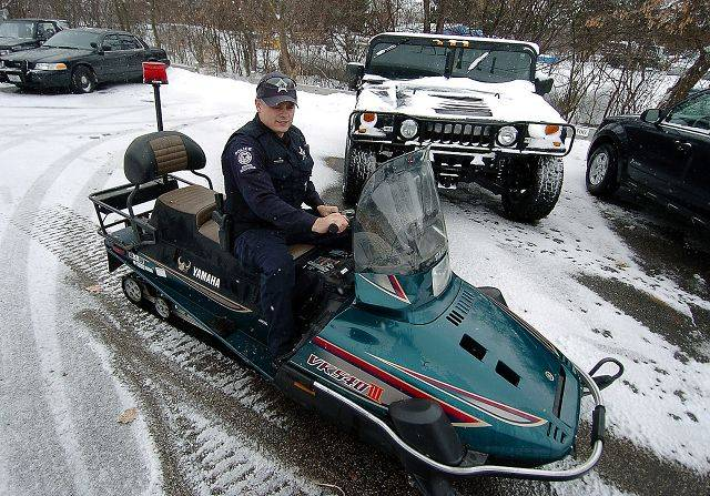 Round Lake Park police officer Waymon Vela prepares a Navy surplus, Arctic Circle-grade snowmobile the department is rolling out to handle blizzard conditions. In the background is an Army surplus Hummer at Round Lake Park's disposal.