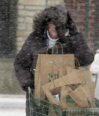 Lynn Moore of Wheaton shields her face from winds and snow as she stocks up on provisions at the Whole Foods in Wheaton Tuesday afternoon.
