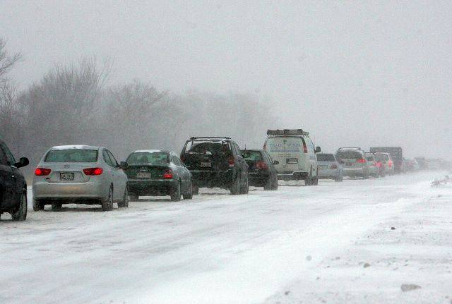 Cars head westbound on Butterfield Road with low visibility as snow started coming down with high winds Tuesday afternoon in Wheaton.
