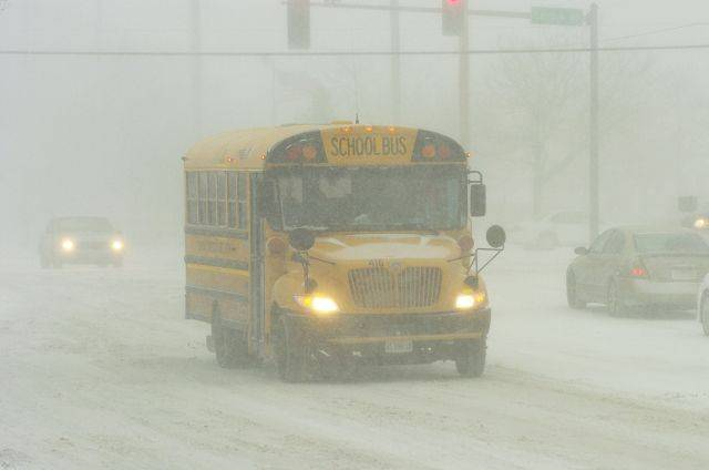 A school bus navigates the intersection of Central and New Wilke roads at the start of Tuesday's blizzard.