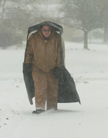 Mike Rivera of Rolling Meadows carries a snowblower canopy home at the start of Tuesday's blizzard.