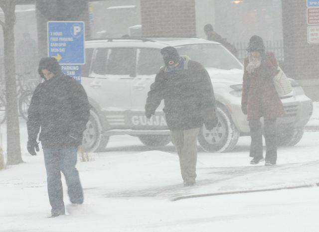 Commuters keep make their way home as the blizzard begins Friday afternoon in Arlington Heights.