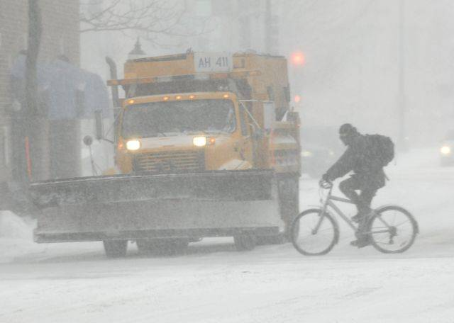 A plow waits for a bicyclist to pass in downtown Arlington Heights as the blizzard begins Tuesday afternoon.