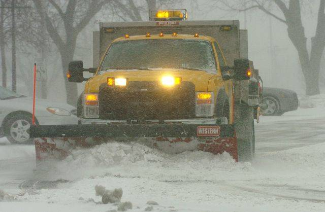A public works truck plows the Rolling Meadows municipal lot at the start of Tuesday's blizzard.