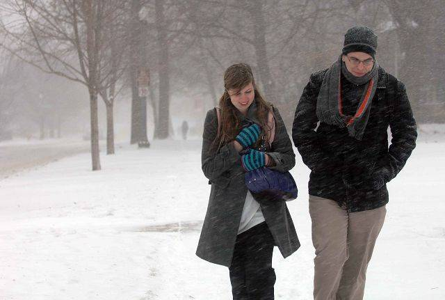 Jackie Niemeyer of Mokena,left, and Brian Failing of Lisle walk to the dorms on the campus of North Central College Tuesday. They were seeking shelter from the cold.