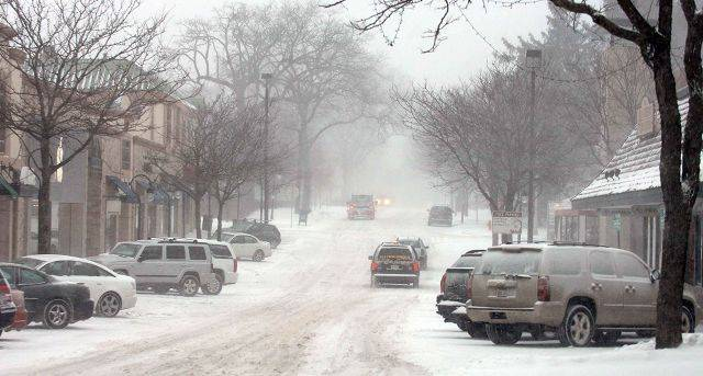 Downtown Naperville is quiet while snow falls Tuesday.