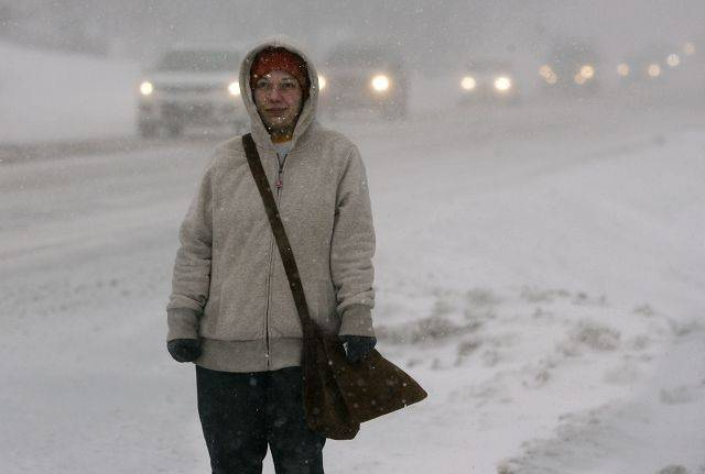 Nicole Podraza of Grayslake stands in a blizzard as along Gages Lake Road in Grayslake waiting for a bus Tuesday.