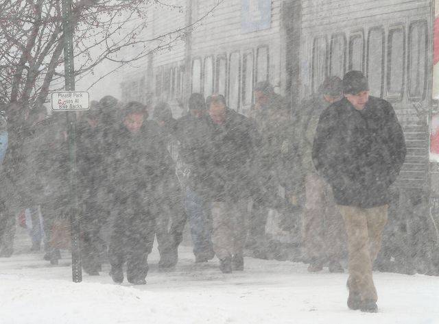 Commuters exit the train to almost white out conditions at the Metra stop in Tuesday afternoon in Libertyville.