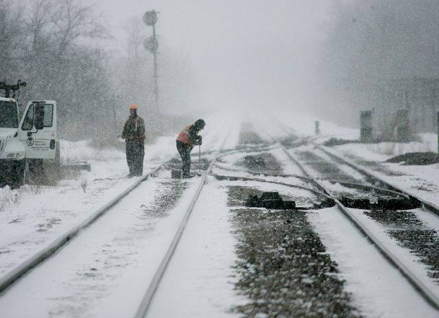 Canadian Pacific Railway employees work on the rail line in the snow Tuesday near Wadsworth Road in Wadsworth.