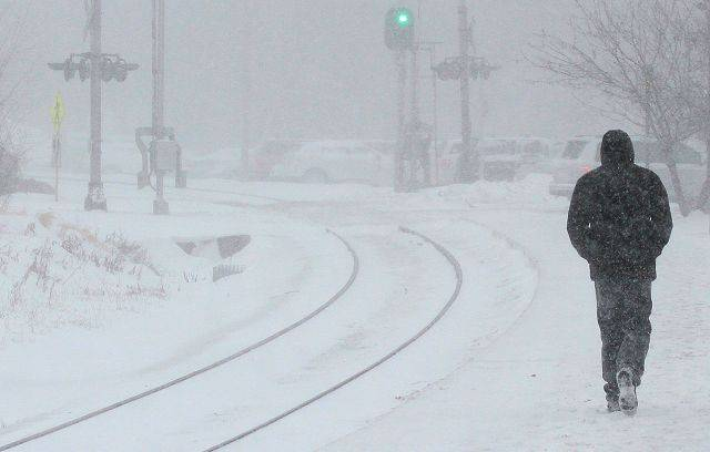 A commuter walks down the platform at the Lubertyville Metra stop as a blizzard hit the area Tuesday afternoon.