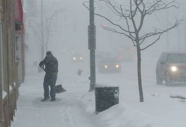 Tony Vazquez tries to keep up with the blizzard by shoveling in front of Bulldogs Grill in downtown Wauconda.