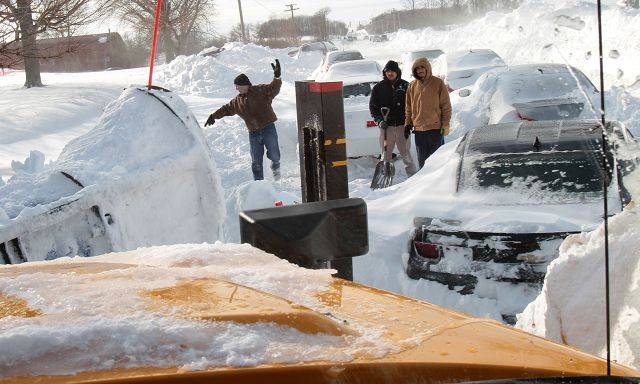 Dan Merz is guided around stranded cars as people dig their cars out from snowdrifts on Peterson Road west of Route 83 Wednesday.