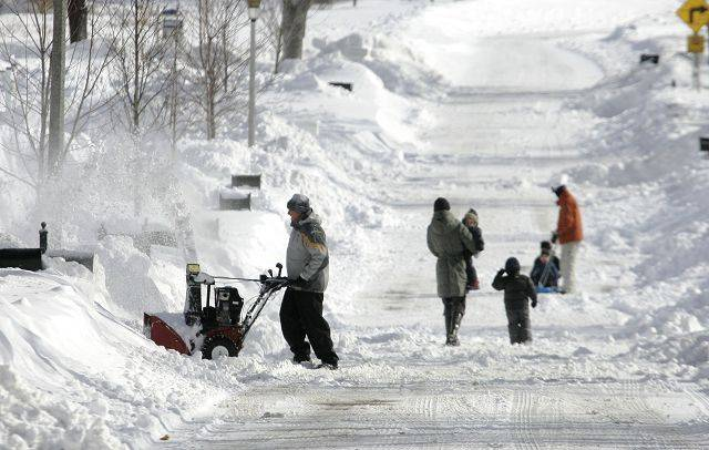 Libertyville residents take to the streets talking to neighbors after the blizzard hit the area Wednesday in Lake County.