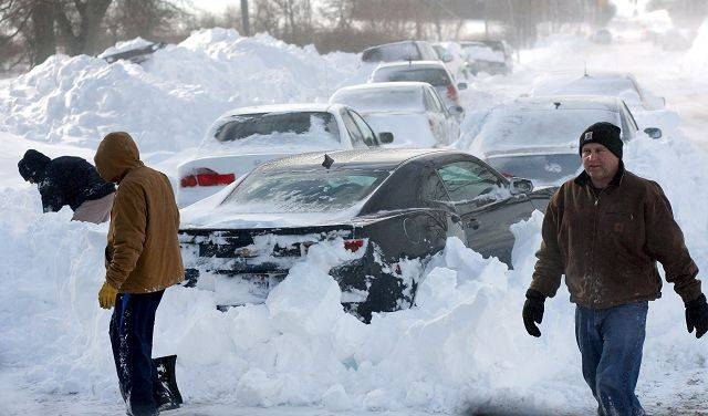 People dig their stranded cars out from snow drifts on Peterson Rd. West of Route 83 Wednesday near Mundelein.
