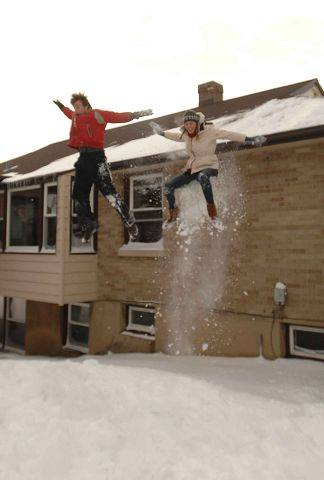 Tom Fowler, left, of Turkey and Jill Ridderboss of St. Louis get ready to jump from a building into a snow drift on the campus of Wheaton College Wednesday.