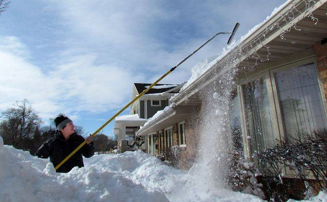 Victoria Zepeda, of Itasca, cleans snow from the roof of her neighbors home Wednesday.