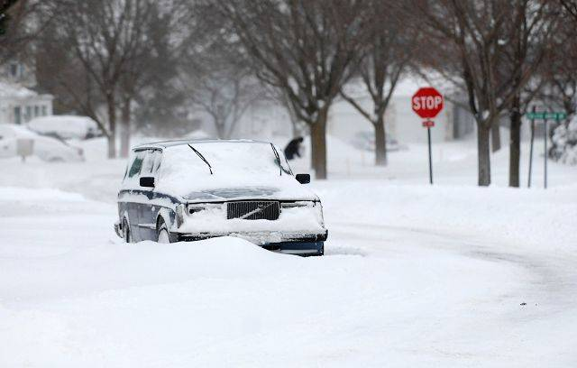 A car stuck in the snow is left in the middle of a street in Elgin Wednesday morning.