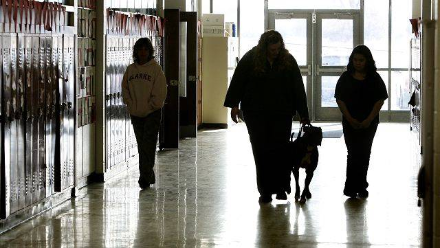 Bitz, a pit bull, is brought in by dog handlers Karen Boeing and Traci McCarthy, left, to sit with fifth-grade reading students at Raymond Ellis School in Round Lake Beach. Jasmin Martinez, 11, is to the right.
