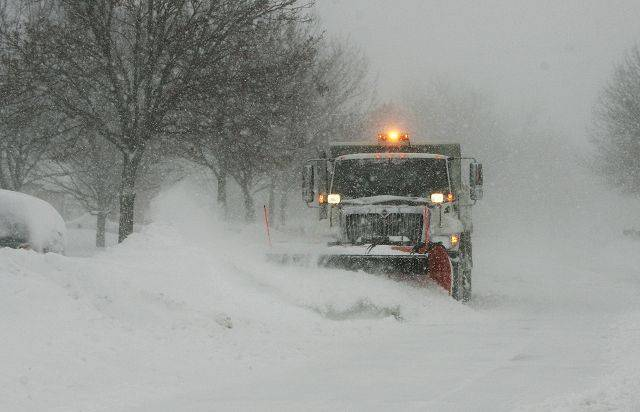 A Mundelein Public Works plow heads down Huntington Drive Wednesday morning attempting to keep up with the snow.