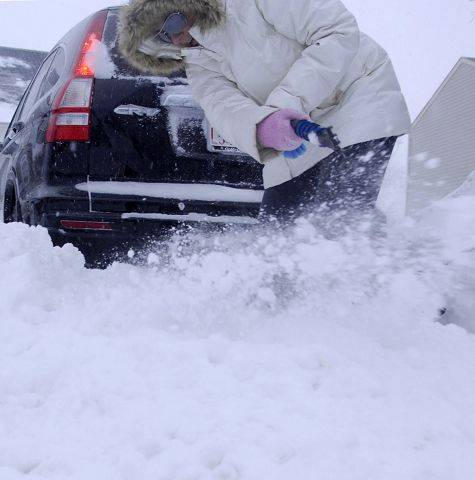 "Saying ""I just want to go home!"", Stephanie Roberts of Elgin helps to dig out her car using an ice scraper Wednesday morning. She stayed at a friends house last night when travel became impossible."