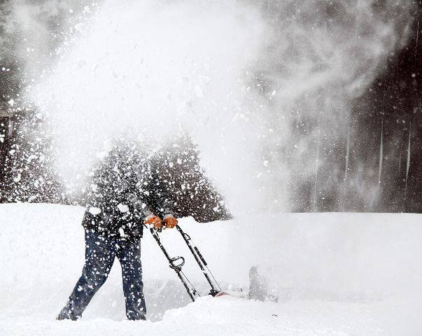 A maintenance worker removes snow from the parking lot at The Clipper's Edge on Dewes Street in Glenview.