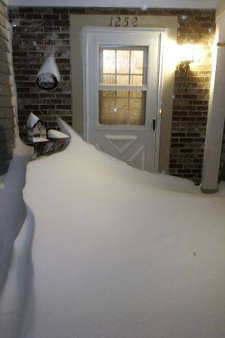 The front entrance of a Mundelein home is blocked by snow drifts after the blizzard swept the area last night in Lake County.
