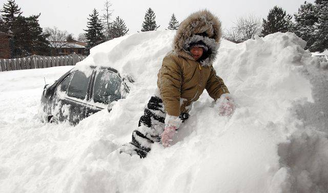 Stacey Colin, 7, of Palatine helps her dad dig their car out from under a huge snow drift Wednesday morning.