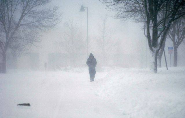 Luis Santos of Elgin walks down College Green Drive Wednesday morning as the snow blows in his face.