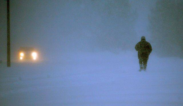 Plows dig out from a pedestrian makes his way through the blizzard in Aurora on Wednesday morning.