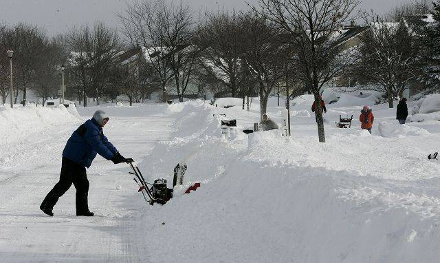 Zibi Szwejkowski uses a snow plower to clear his driveway in Mundelein as other neighbors work on theirs Wednesday in Lake County.