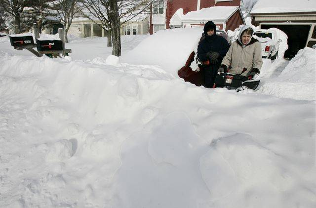 Richard Liss, left, and Betty Fox of Mundelein clear their driveway Wednesday morning.