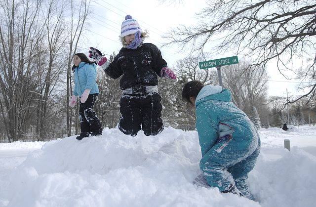Jenna Dubinski, 7, jumps off a snow mound piled at the corner of Hanson Ridge and Hanson Road with friends Cynthia and Samantha Delgado, both 8, in Lily Lake on Wednesday.