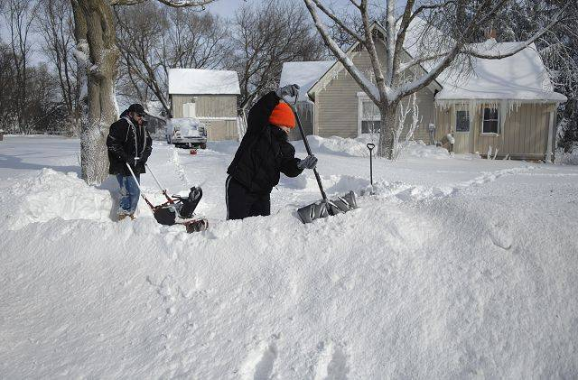 Jim Appleberg and daughter Katie, 15, use teamwork to dig out their driveway on Hanson Road in Lily Lake on Wednesday.